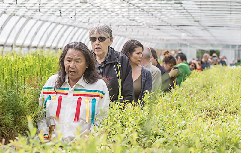 George Desjarlais sings a prayer of blessing as he leads a group through the greenhouse.   Photograph By Trent Ernst